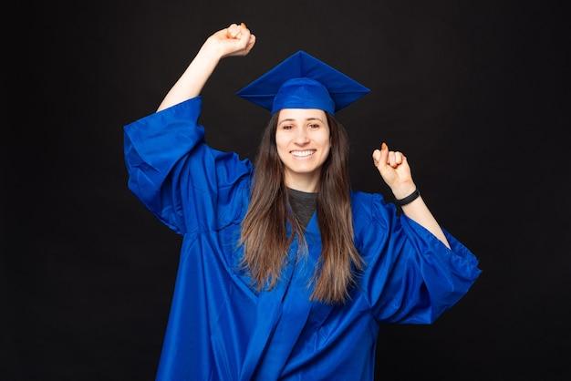 Charmante jeune femme étudiante en baccalauréat et chapeau de graduation célébrant