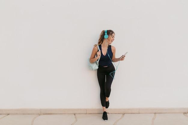 Charmante jeune femme joyeuse en tenue de sport appréciant le chat au téléphone, belle musique dans les écouteurs. outwork, style de vie sportif, modèle à la mode, temps pour le fitness, s'amuser
