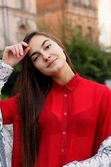Charmante jeune femme avec une magnifique chevelure brune, de grands yeux, un magnifique rouge à lèvres et un look élégant. une jeune femme séduisante se précipite dans le centre-ville, elle se tourne vers la caméra et sourit.