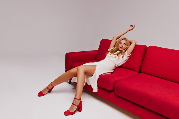 Charmante jeune femme en robe blanche assise sur l'entraîneur portrait de femme bouclée rêveuse posant sur le canapé.