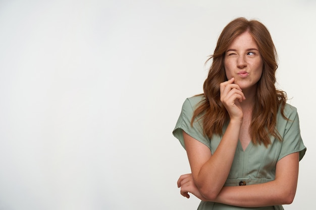 Charmante jeune femme rousse posant, s'appuyant sur son menton et pinçant les lèvres, regardant de côté avec les yeux fermés