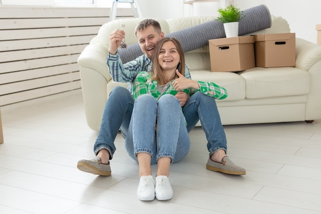 Charmante jeune femme et son mari tenant en mains les clés de leur nouvel appartement en position assise