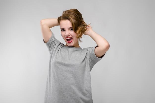 Charmante jeune femme en t-shirt gris. la femme tient ses mains derrière sa tête et crie