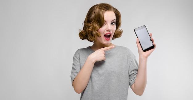 Charmante jeune femme en t-shirt gris. une femme tient un téléphone dans sa main