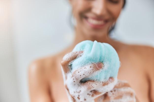 Charmante jeune femme tenant une éponge de bain en luffa