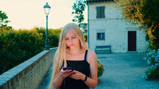 Charmante jeune femme utilisant un smartphone en marchant dehors en été. elle lit quelque chose et discute.