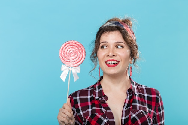 Charmante jeune femme en vêtements rétro tenant des sucettes colorées dans ses mains et en léchant une posant sur fond bleu. concept d'amour pour les bonbons et les vacances. espace de copie