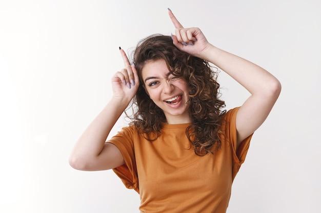 Charmante jeune fille arménienne rebelle espiègle et mignonne veut s'amuser en se relaxant dans le spectacle de la danse de la langue mettre la tête de l'index imitant les cornes du diable, debout sur fond blanc