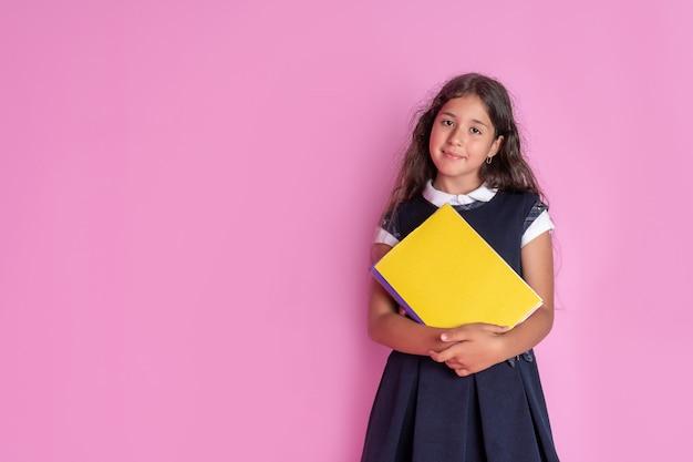 Une charmante jeune fille aux longs cheveux noirs bouclés dans un uniforme scolaire avec un livre dans ses mains