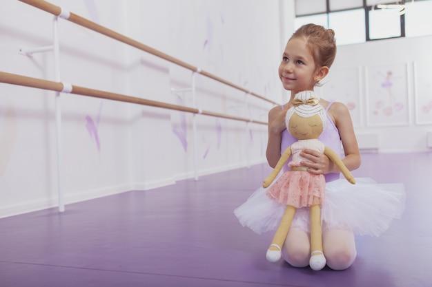 Charmante jeune fille ballerine assise sur le sol à l'école de ballet, tenant une poupée ballerine