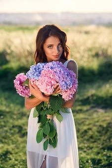 Une charmante jeune fille avec un beau sourire dans une robe blanche avec un bouquet de fleurs aux couleurs tendres au coucher du soleil.
