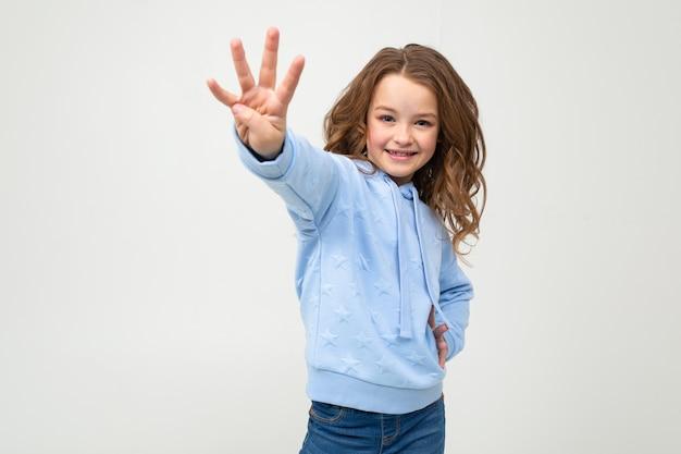 Charmante jeune fille dans un sweat à capuche bleu montre quatre doigts sur un mur gris clair