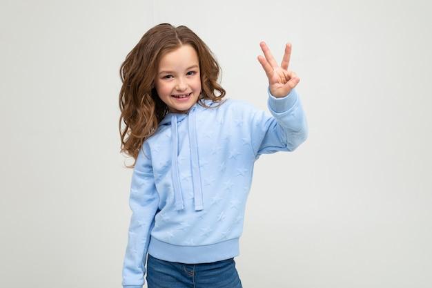 Charmante jeune fille dans un sweat à capuche bleu montre trois doigts sur un mur gris clair