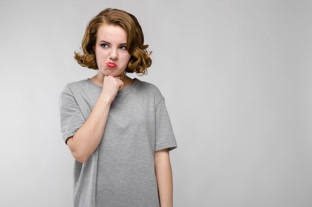 Charmante jeune fille dans un t-shirt gris sur fond gris. la fille a épinglé son menton