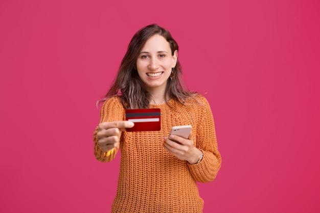 Charmante jeune fille debout sur un espace rose et montrant sa carte de crédit et tenant un smartphone