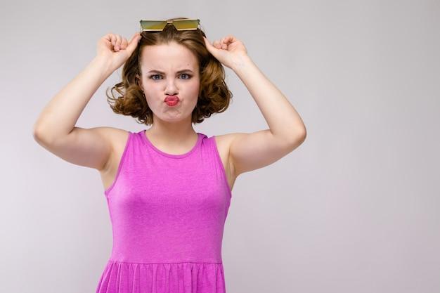 Charmante jeune fille en robe rose sur gris jeune fille dans des lunettes carrées la jeune fille a levé ses lunettes sur sa tête
