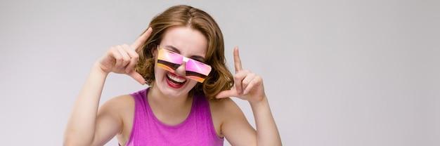 Charmante jeune fille en robe rose. joyeuse fille dans des verres carrés. la fille pointe les doigts en haut