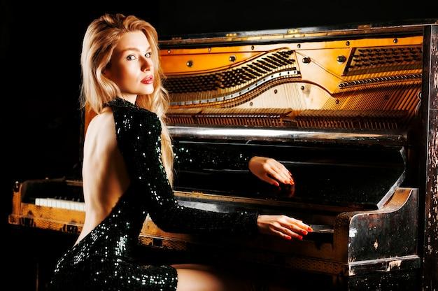 Charmante jeune fille en robe de soirée posant près du vieux piano allemand