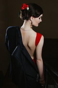 Une charmante jeune fille sensuelle vêtue d'une robe et d'une veste élégantes se promène en cas de figure