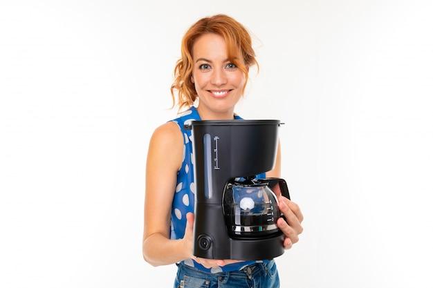 Charmante jeune fille sourit et détient une machine à café sur fond blanc