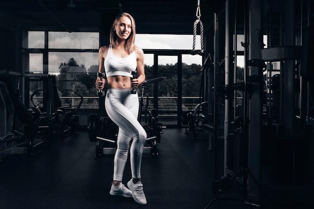 Charmante jeune sportive posant dans la salle de gym. concept de musculation