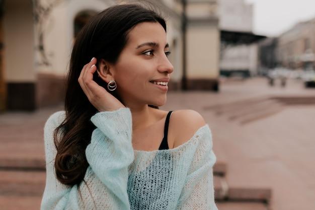 Charmante jolie dame aux cheveux noirs portant un pull à la menthe posant sur la vieille ville