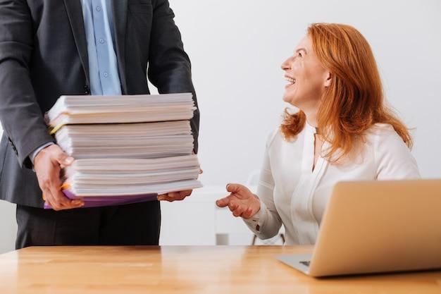 Charmante jolie femme joyeuse se sentir enthousiaste tout en recevant une pile de documents s
