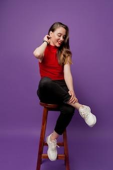 Charmante jolie fille en haut rouge assis sur une chaise et regardant de côté avec un beau sourire sur violet
