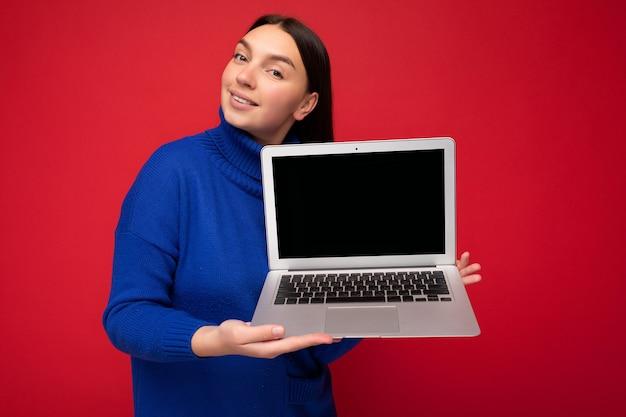 Charmante jolie jeune femme étudiante brunet heureuse tenant un ordinateur portable regardant la caméra en pull bleu isolé sur fond de mur rouge. maquette