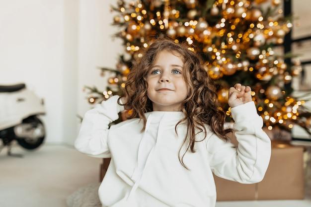 Charmante jolie petite fille avec des boucles en vêtements blancs souriant devant l'arbre de noël avec des lumières