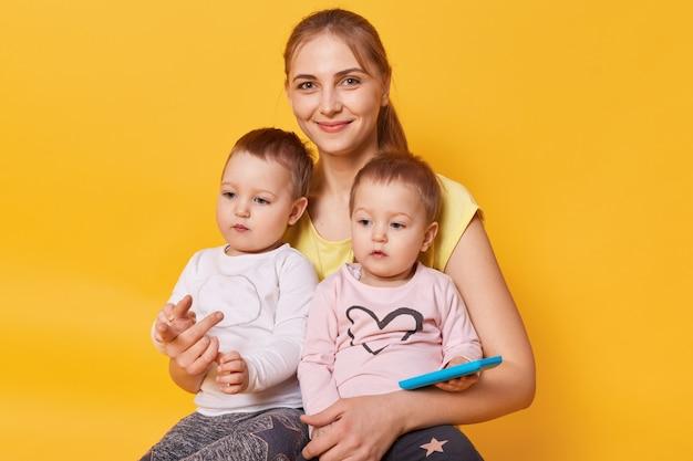Charmante maman affectueuse assise avec ses mignonnes petites filles sur le sol en studio jaune