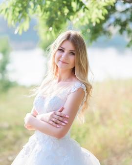 Charmante mariée a l'air heureux de poser dans sa magnifique robe à l'extérieur dans une journée d'été ensoleillée
