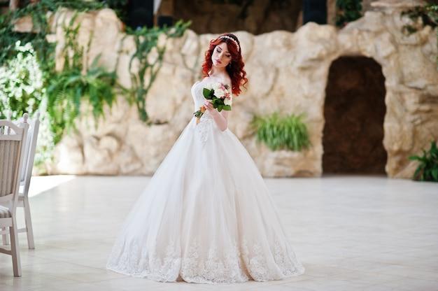 Charmante mariée aux cheveux roux avec bouquet de mariée