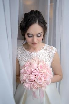 Charmante mariée à la fenêtre avec un bouquet de mariée