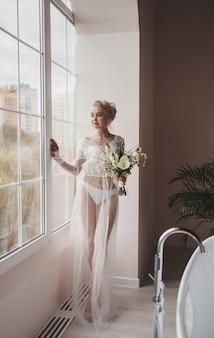 Charmante mariée avec des fleurs de mariage debout près de la fenêtre