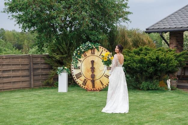 La charmante mariée garde un bouquet de mariage et marche le long de la cour