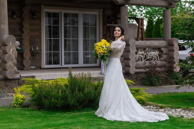 La charmante mariée garde un bouquet de mariage et pose sur la cour