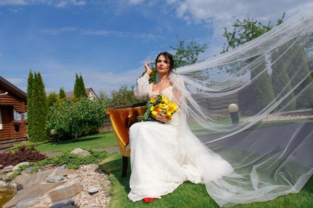 La charmante mariée garde un bouquet de mariage et s'assoit dans la cour