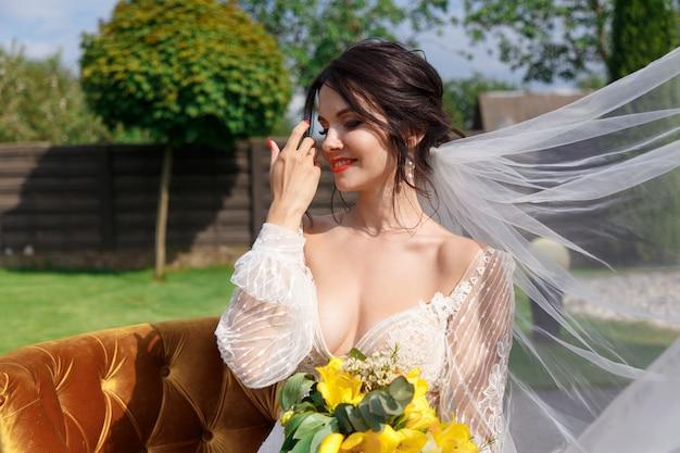 La Charmante Mariée Garde Un Bouquet De Mariage Et S'assoit Dans La Cour Photo Premium