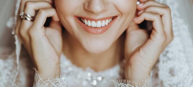 Charmante mariée avec une peau parfaite touche sa tendre boucle d'oreille