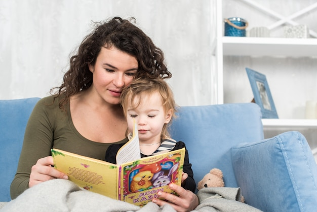 Charmante mère montre des images dans un livre à sa petite fille mignonne à la maison.