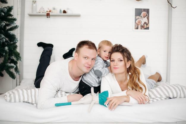 Charmante mère et père avec petit fils mignon couché ensemble sur le lit, regardant à l'avant et posant en studio en hiver