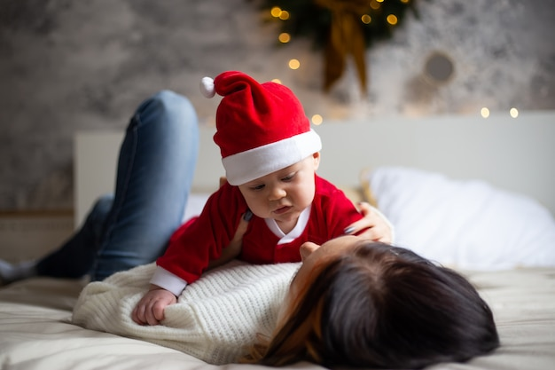 Charmante mère regarde son petit fils enfant en bas âge et souriant sur le fond des arbres de noël et des guirlandes dans la maison