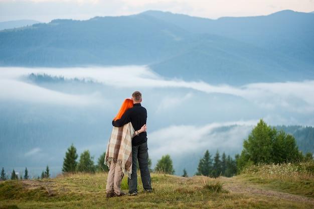 Charmante paire debout sur une colline profitant d'une brume matinale sur les montagnes. jeune couple s'embrassant. la fille rousse est couverte d'une couverture. vue arrière