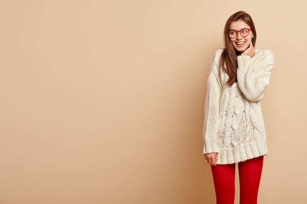 Charmante petite amie féminine tendre exprime une attitude optimiste et de bonheur, sourit joyeusement, concentrée de côté