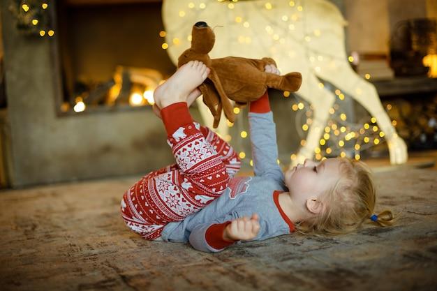 Charmante petite blonde sur le tapis de la maison décorée pour noël. noël confortable