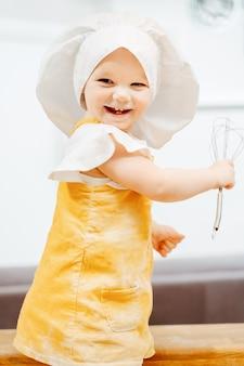 Charmante petite fille d'un an et demi dans un costume de cuisinier