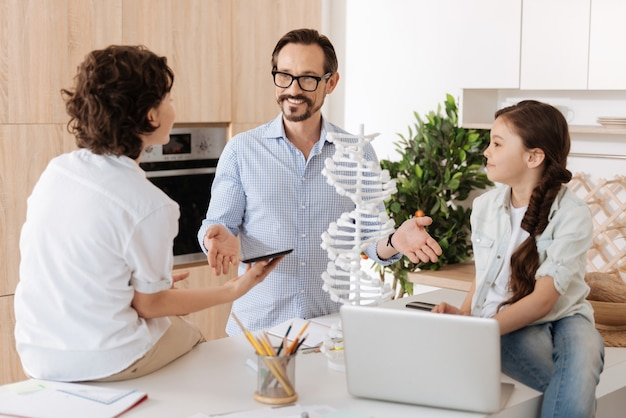 Charmante petite fille assise sur le comptoir de la cuisine ainsi que son frère tenant une tablette et parlant avec le père faisant un geste explicatif