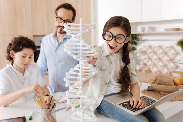 Charmante petite fille assise sur le comptoir de la cuisine avec un ordinateur portable sur ses genoux et touchant un modèle adn pendant que son père et son frère aîné font des sommes