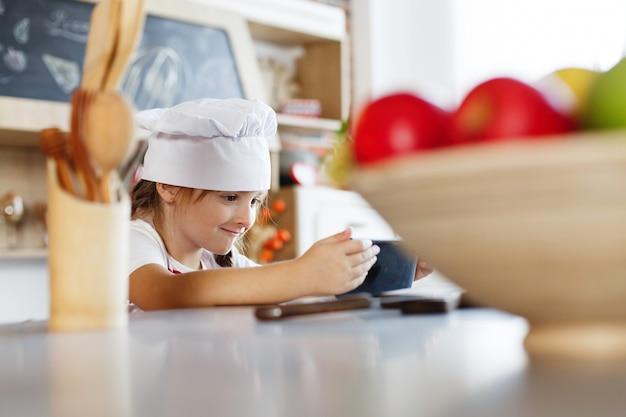 Charmante petite fille au chapeau en chef se dresse devant une table prête à cuire